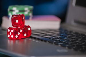 16996410-gambling-chips-and-red-dice-on-laptop-keyboard-background